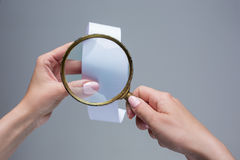 The female hands with  empty transaction paper or paper check and magnifier. The female hands with  empty transaction paper or paper check on gray background and Royalty Free Stock Photos