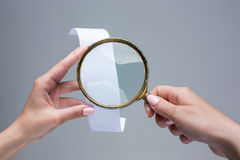 The female hands with  empty transaction paper or paper check and magnifier. The female hands with  empty transaction paper or paper check on gray background and Royalty Free Stock Photo