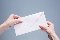 The female hands with envelope against the gray background. The female hands with the envelope against the gray background Royalty Free Stock Photos