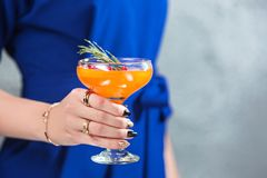 The exotic cocktail and female hands. The female hands and exotic cocktail at studio Royalty Free Stock Images
