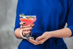 The exotic cocktail and female hands. The female hands and exotic cocktail at studio Royalty Free Stock Photography