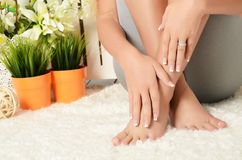 Female hands and feet with manicure and a pedicure Stock Photos