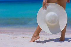 Female hands and feet with white hat on the beach. Blue sea and sky background stock photography