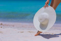 Female hands and feet with white hat on the beach. Blue sea and sky background royalty free stock photography