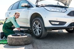 Mechanic lifting up broken car with jack.  royalty free stock images