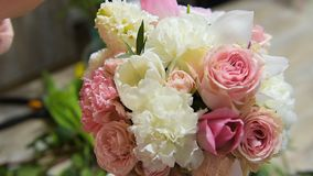 Arrange flowers in bouquet in flower shop. Female hands fix flowers in pink and white composition. Arrange flowers in bouquet in flower shop stock video footage