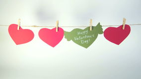 Female hands fixing a green heart with congratulation and wings with a clothespin on a cord. White background. Female hands fixing a green heart with stock video footage