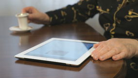 Female hands flipping through the magazine using a digital tablet. Closeup stock video