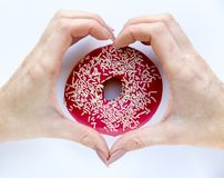 Female hands in the form of heart against donut, top. View royalty free stock image