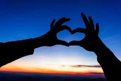 Female hands in the form of heart against the sky pass sun beams. Hands in shape of love heart. Female hands in the form of heart against the sky pass sun beams royalty free stock image