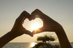 Female hands in the form of heart against the sky pass sun beams. Hands in shape of love heart stock photos