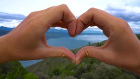 Female hands in the form of heart against Toba lake, North Sumatra, Indonesia. stock footage