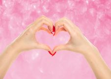 Female hands in the form of heart. On abstract background with blurred lights stock photos