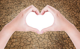 Female hands in the form of heart. Isolated on cracked earth background royalty free stock image