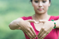 Female hands in the form of heart on nature background. Female hands in the form of heart on nature royalty free stock photos