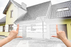 Female hands framing custom house design. Combination drawing and photo Royalty Free Stock Image