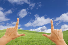 Female Hands Framing Deep Blue Sky Above Grass Field royalty free stock image
