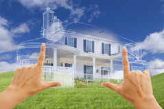 Female Hands Framing House Drawing and House Above Grass. Female Hands Framing Beautiful Custom House Drawing and Ghosted House Above Grass Field stock image