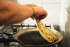 Female hands fry in a frying pan a classic Caucasian. Dish of khychin in the kitchen in a mountain village Royalty Free Stock Photography