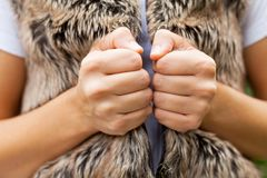 Female hands & fur vest. Close up female hands holding fluffy fur vest stock photos