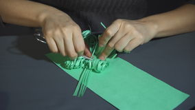 Female hands gently frizzing thinly fringed green paper with metal scissors. stock footage