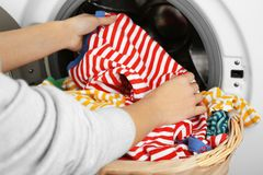 Female hands getting out clean clothes. From washing machine Stock Photo