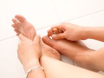 Female hands giving massage to bare foot Royalty Free Stock Images
