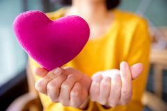 Female hands giving pink heart pillow and make a symbol of heart love with fingers. Female hands giving red heart pillow and mini heart- safety concept. Vintage royalty free stock photo