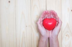 Female hands giving red heart. On wood table background stock images