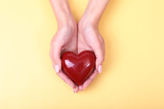 Female hands giving red heart, isolated on gold background Stock Images