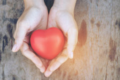 Female hands giving red heart overhead of wooden planks in the morning light. Filtered color. vintage tone. Stock Images
