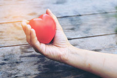 Female hands giving red heart overhead of wooden planks in the morning light. Filtered color. vintage tone. Royalty Free Stock Images