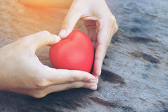 Female hands giving red heart overhead of wooden planks in the morning light. Filtered color. vintage tone. Royalty Free Stock Photo