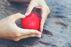 Female hands giving red heart. vintage tone Royalty Free Stock Images