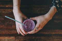 Female hands with a glass of smoothies. Hands of the girl holding a glass with blueberry smoothies in a cafe on the background of a wooden table, a girl with Stock Photography