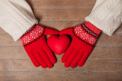 Female hands in gloves holding heart shaped toy on the wonderful. Brown wooden background stock images