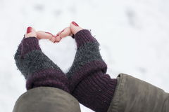 Female hands in gloves holding a snow shaped heart Stock Image