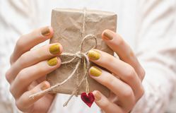 Female hands with gold nail design. Holding a present Stock Photo