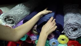 Tailor touching fabric rolls lying in pile in fashion atelier