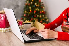 Young woman shopping for christmas presents online stock photography