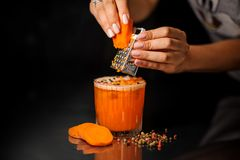 Female hands grating the carrots into the healthy cocktail with pepper Royalty Free Stock Image