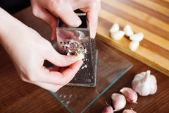 Female hands  grating garlic Royalty Free Stock Image