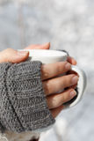 Female hands in gray fingerless mittens with white cup of tea in Stock Image