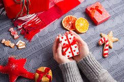 Female hands in gray knitted sweater holding gift box on Christm. Female hands in gray knitted sweater holding romantic gift box with Christmas decor on Royalty Free Stock Photography