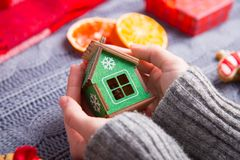 Female hands in gray knitted sweater holding green wooden house. With Christmas decor on background. New Year decoration with dried citrus fruits, cookies Stock Photography