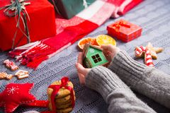 Female hands in gray knitted sweater holding green wooden house. With Christmas decor on background. New Year decoration with dried citrus fruits, cookies Royalty Free Stock Image