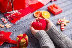 Female hands in gray knitted sweater holding red heart on Christ. Female hands in gray knitted sweater holding red heart with Christmas decor on background. New stock image