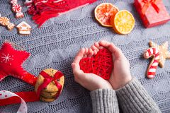 Female hands in gray knitted sweater holding red heart on Christ. Female hands in gray knitted sweater holding red wicker rattan heart with Christmas decor on Stock Photos