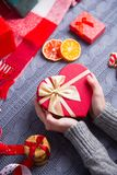 Female hands in gray knitted sweater holding romantic gift on Ch. Female hands in gray knitted sweater holding gift box in shape of heart with Christmas decor on Stock Image