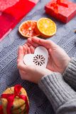Female hands in gray knitted sweater holding heart on Christmas. Female hands in gray knitted sweater holding white heart with Christmas decor on background. New stock images